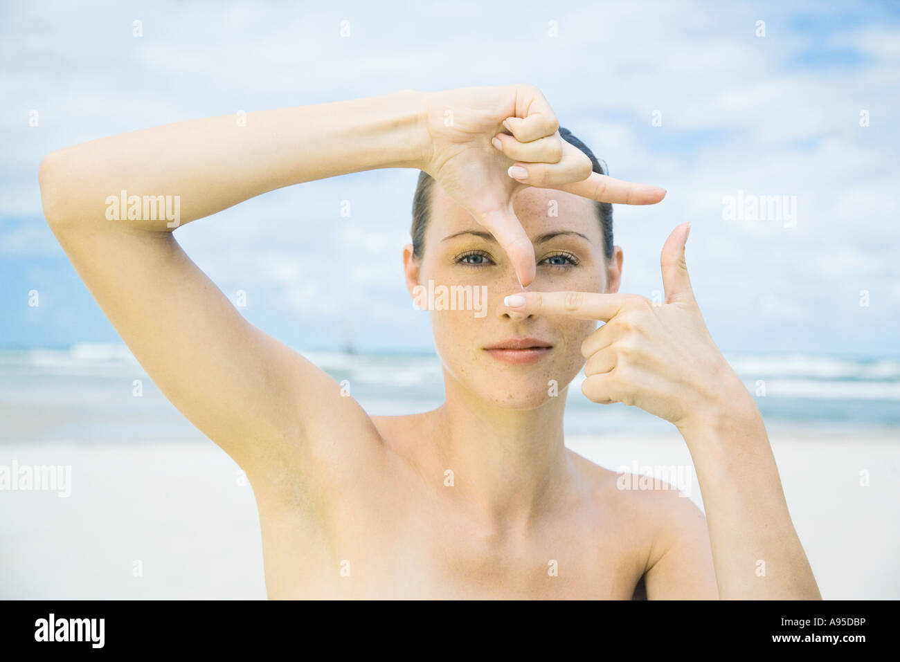 Woman on beach making finger frame around eye, head and shoulders - Stock Image