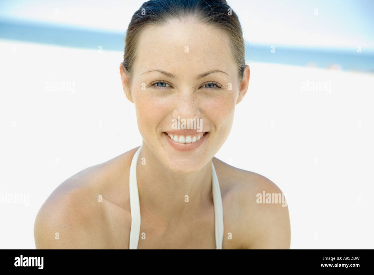 Woman on beach, smiling at camera, head and shoulders - Stock Image