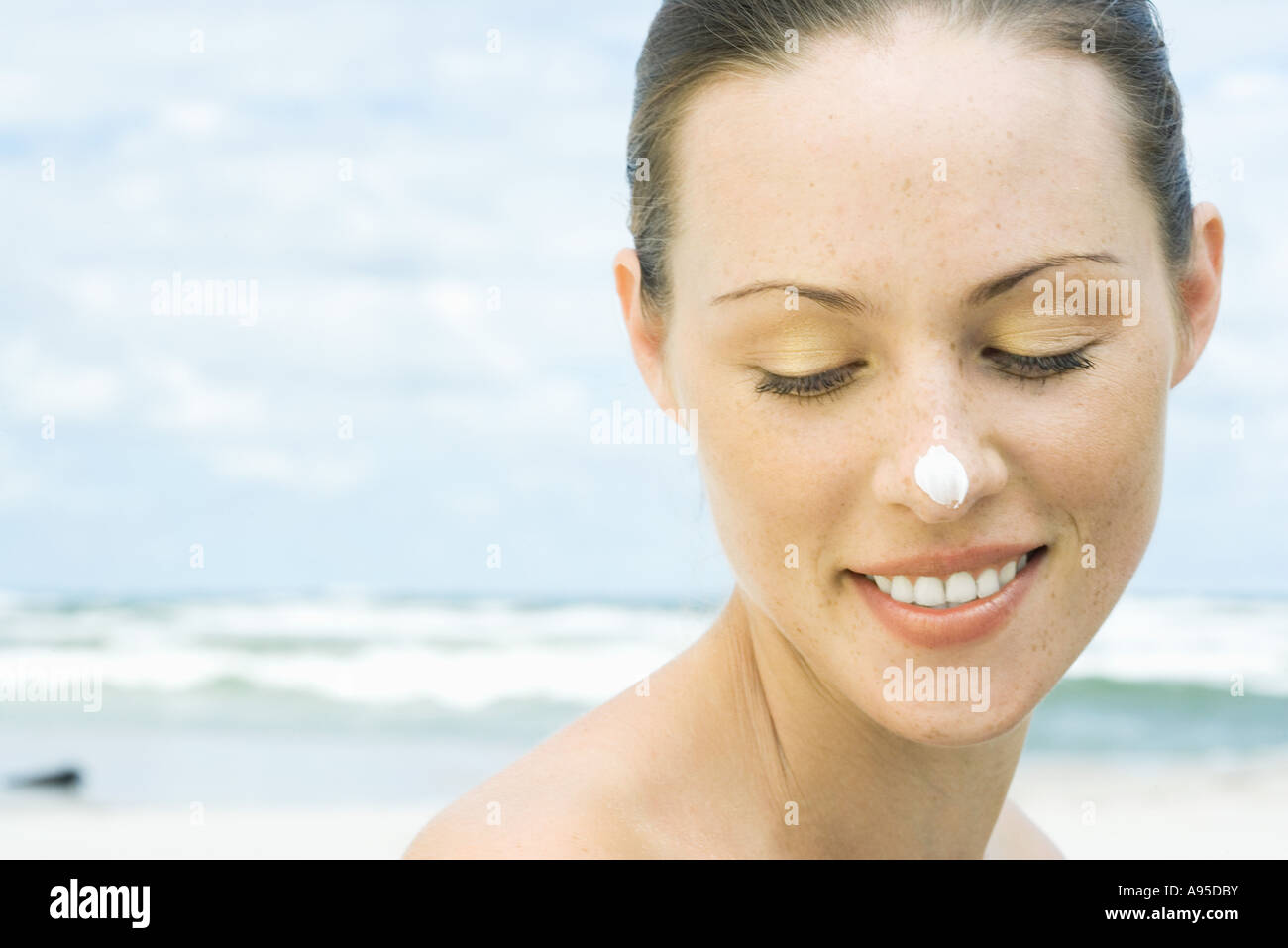 Woman on beach with sunscreen on nose, head and shoulders - Stock Image