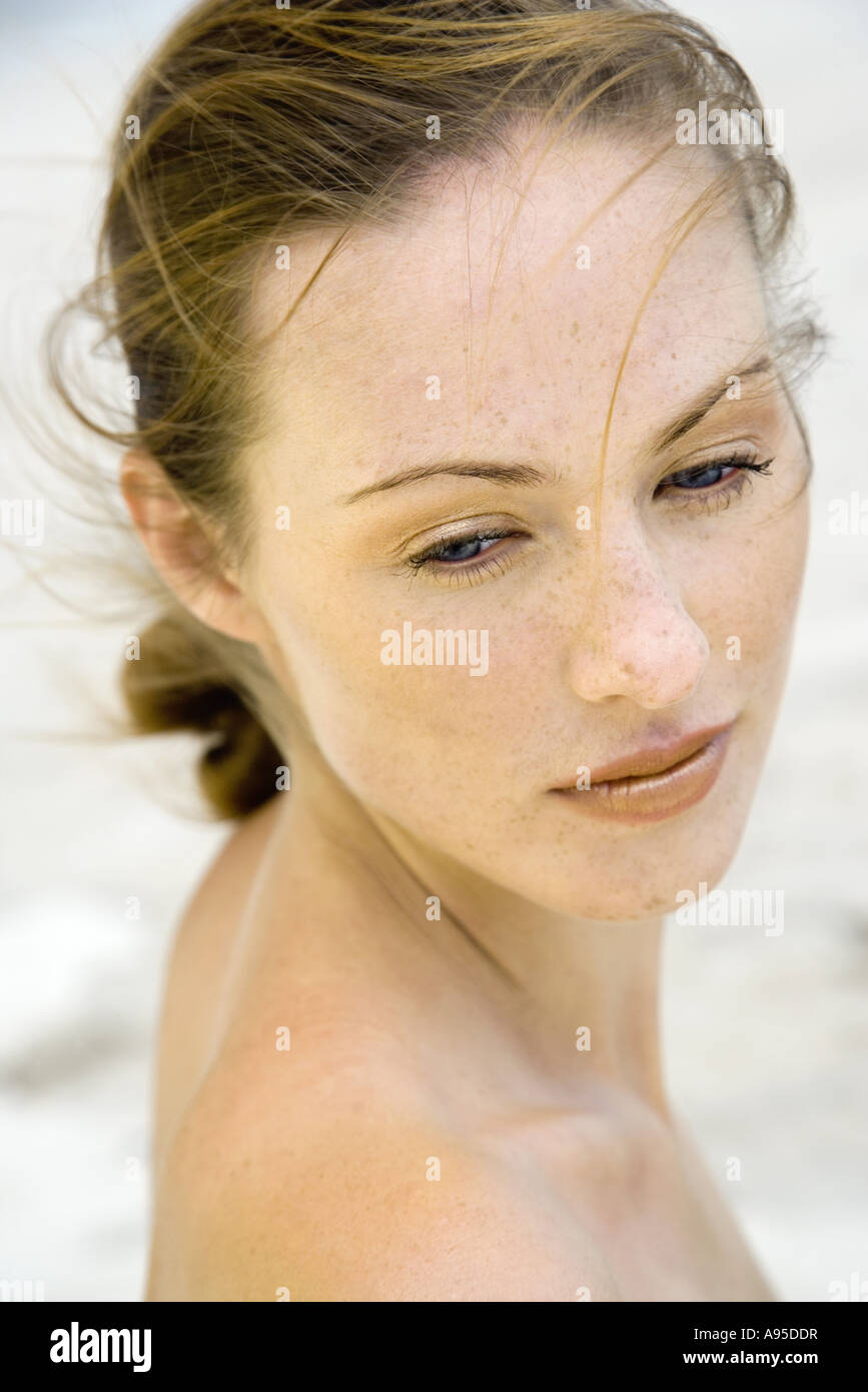 Woman looking over shoulder, hair being tousled by the wind, head and shoulders Stock Photo