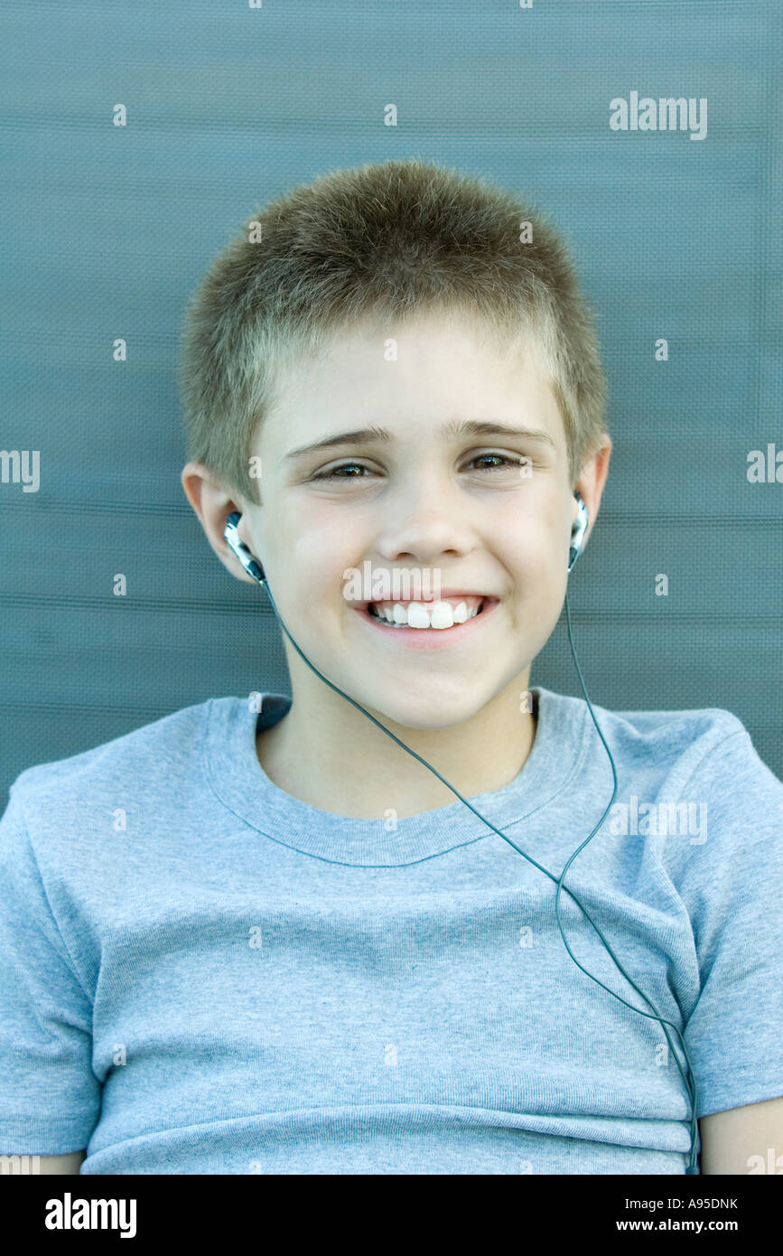 Boy listening to earphones, smiling at camera, portrait - Stock Image
