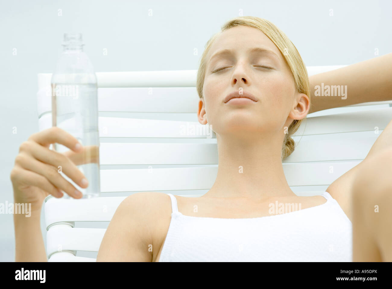 Teenage girl sitting on lounge chair, holding bottle of water, eyes closed - Stock Image