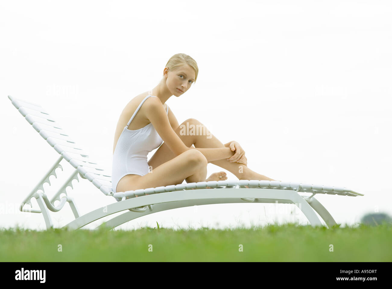 Teenage girl in swimsuit sitting on lounge chair - Stock Image