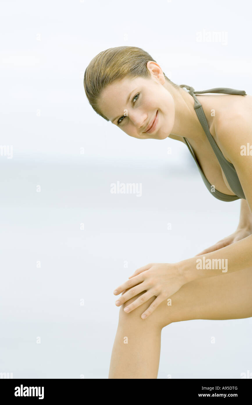 Young woman wearing bathing suit, leaning forward with hands on knee Stock Photo