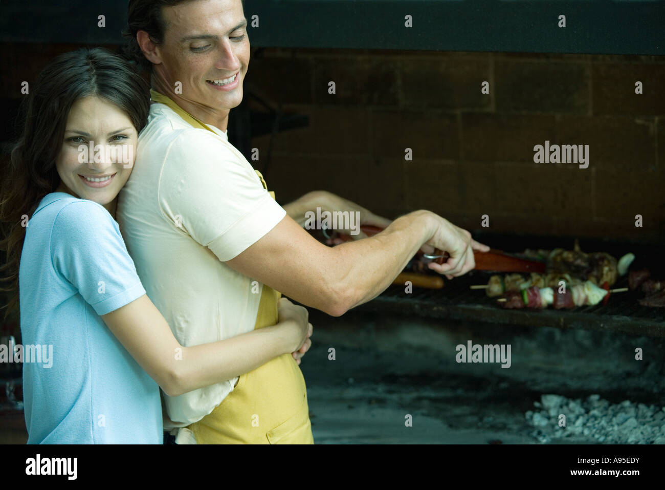 Couple having cookout, woman hugging man from behind - Stock Image