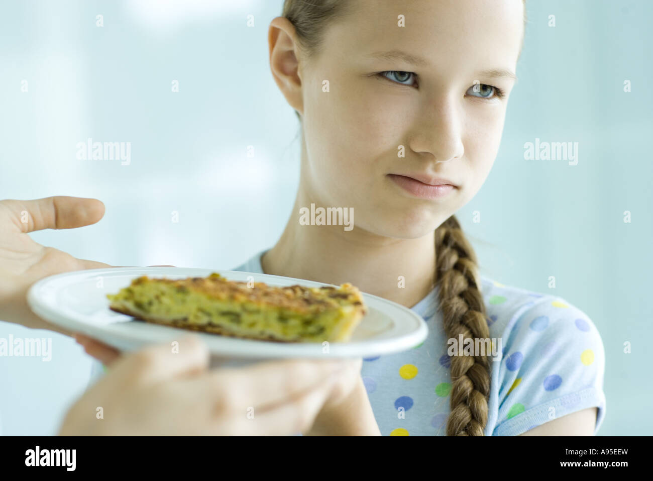 Hands holding up slice of quiche toward girl, girl making face and looking away - Stock Image
