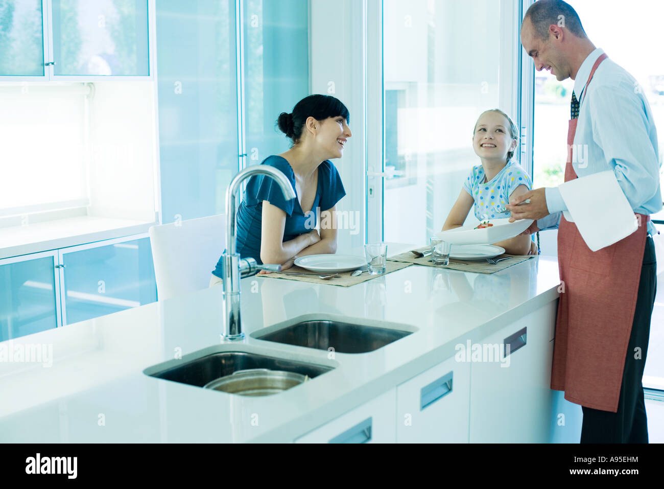 Man serving woman and girl in kitchen Stock Photo: 12257263 - Alamy