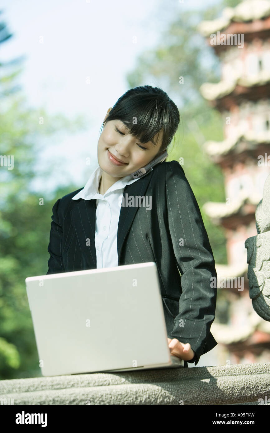 Young woman using laptop and cell phone - Stock Image