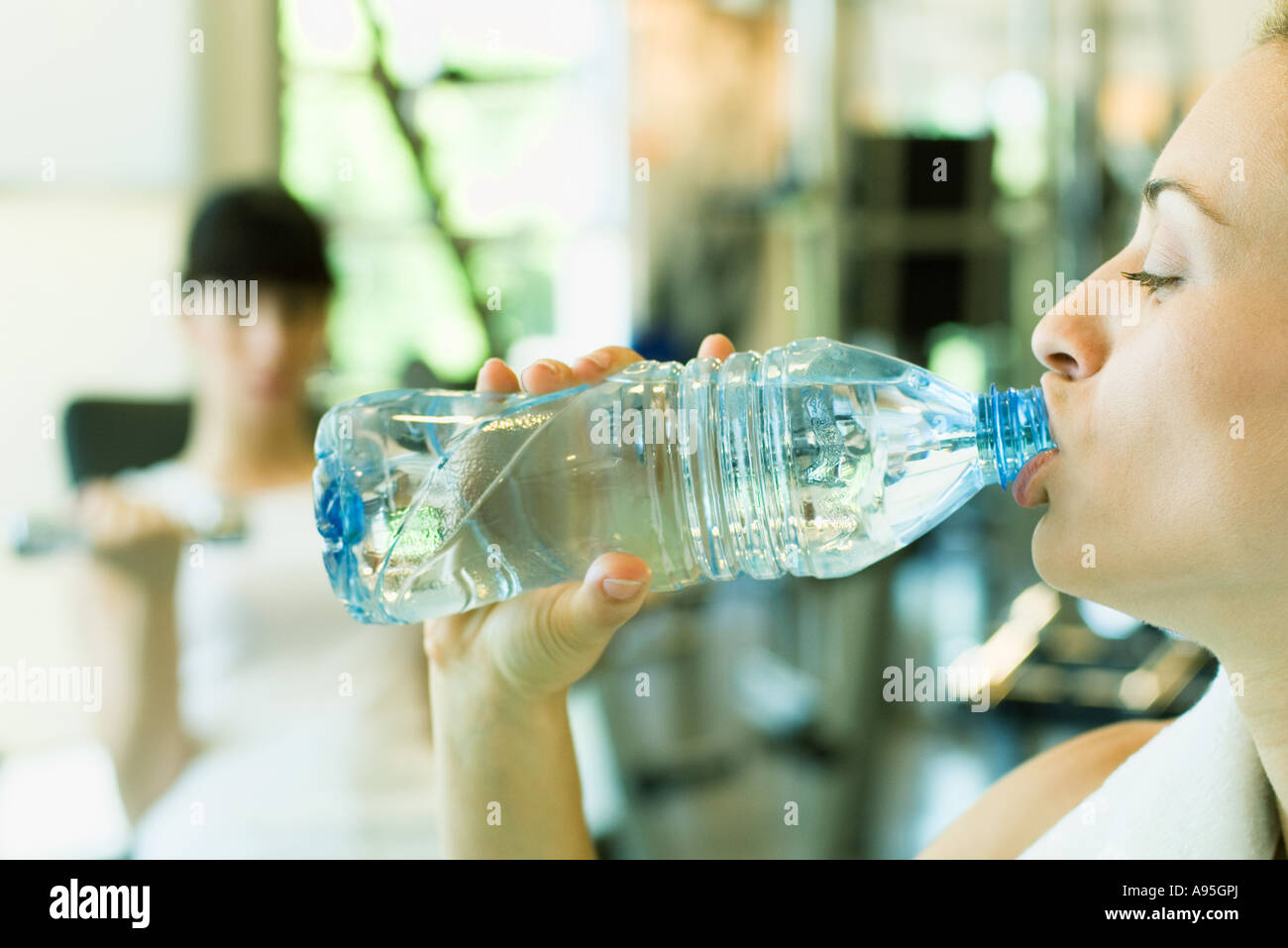 Two women in weight room, focus on woman in foreground drinking bottle of water - Stock Image