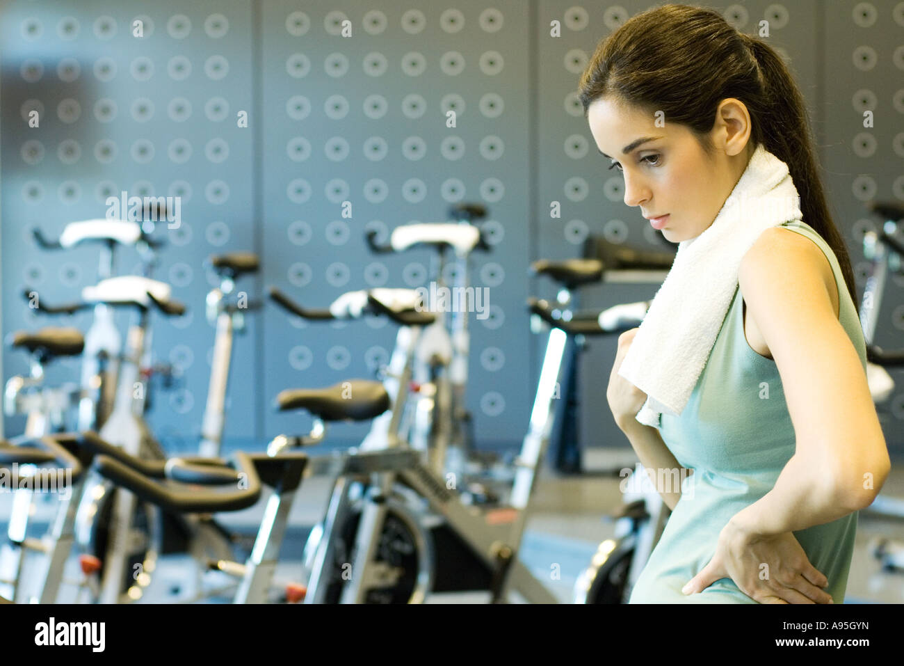 Woman standing in front of exercise bikes, hands on hips - Stock Image