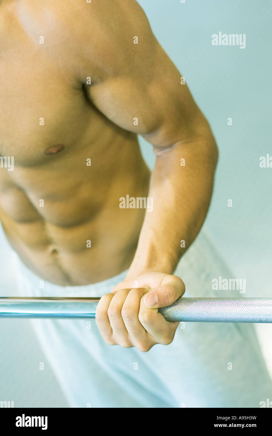 Man lifting barbell, close-up of mid section - Stock Image