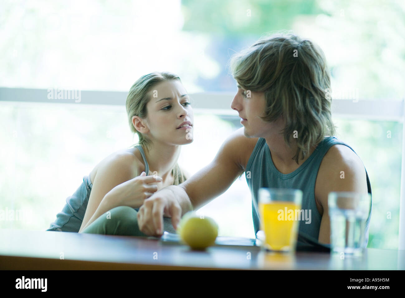 Young couple wearing exercise clothes, sitting side by side, having healthy snack and looking at magazine - Stock Image