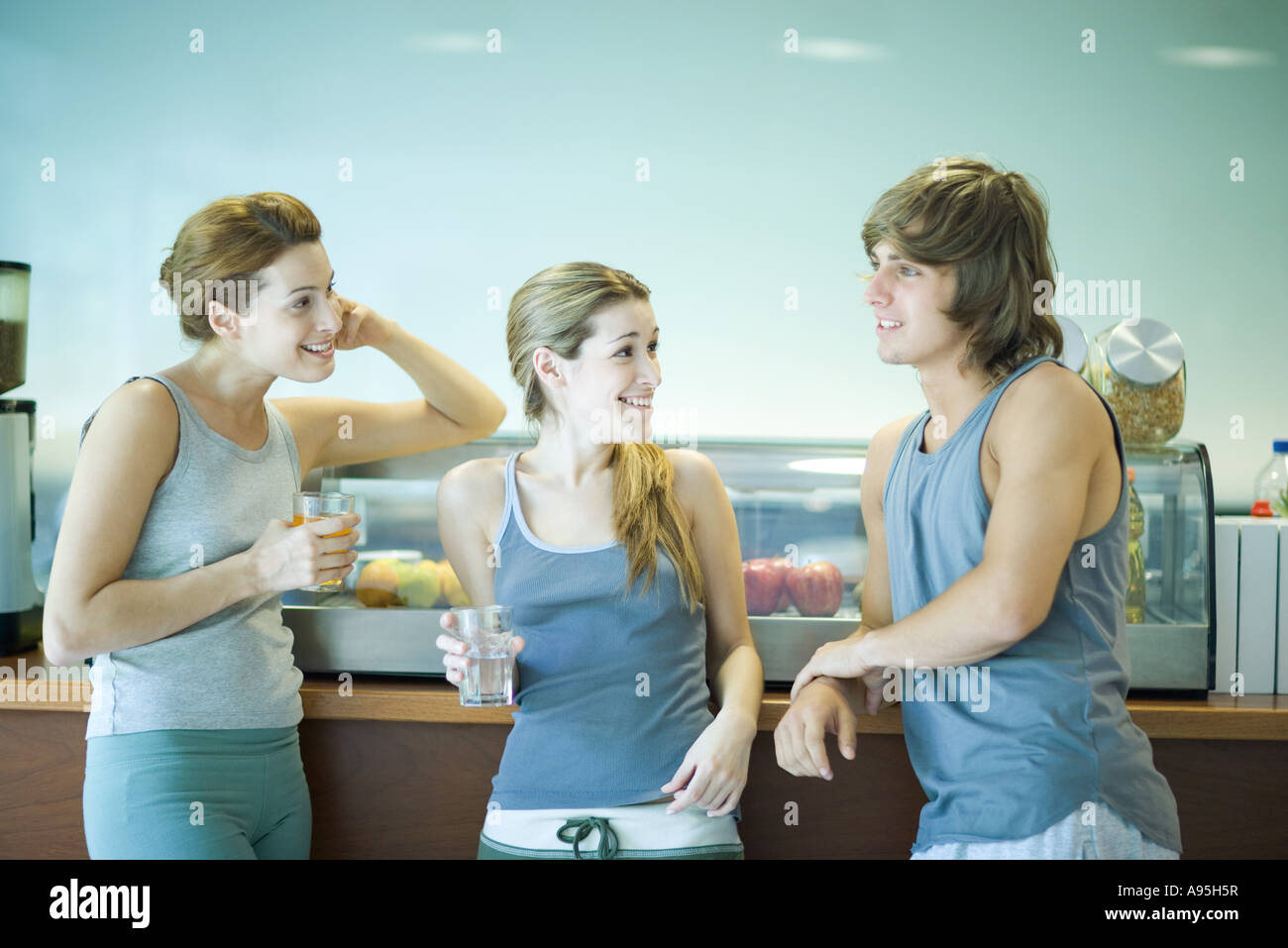 Young adults wearing exercise clothes, standing in cafeteria, having healthy snack and chatting - Stock Image