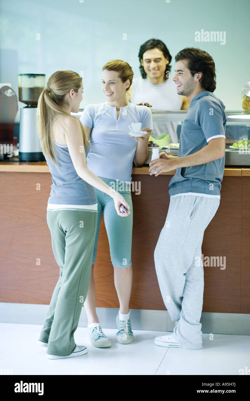Young adults dressed in exercise clothes, standing by snack bar, chatting - Stock Image