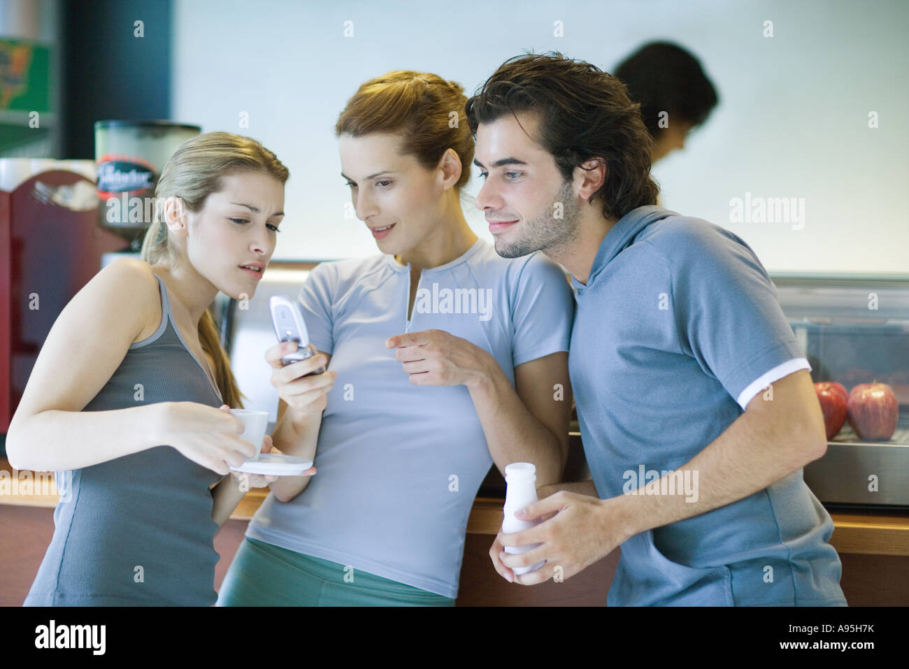 Young adults dressed in exercise clothes, standing by snack bar, looking at cell phone - Stock Image