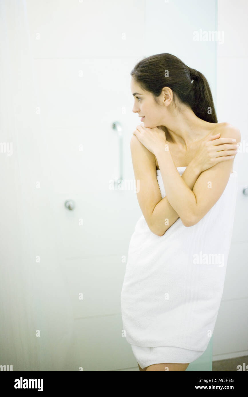 Woman standing wrapped in towel, hands on shoulders, looking away - Stock Image