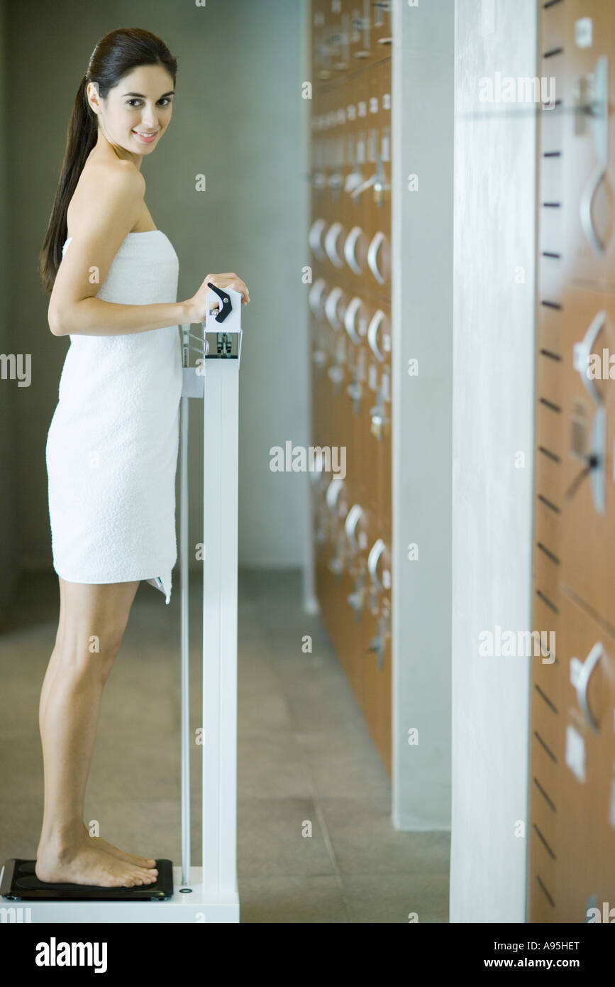 Woman wrapped in towel, standing on scale, looking at camera - Stock Image