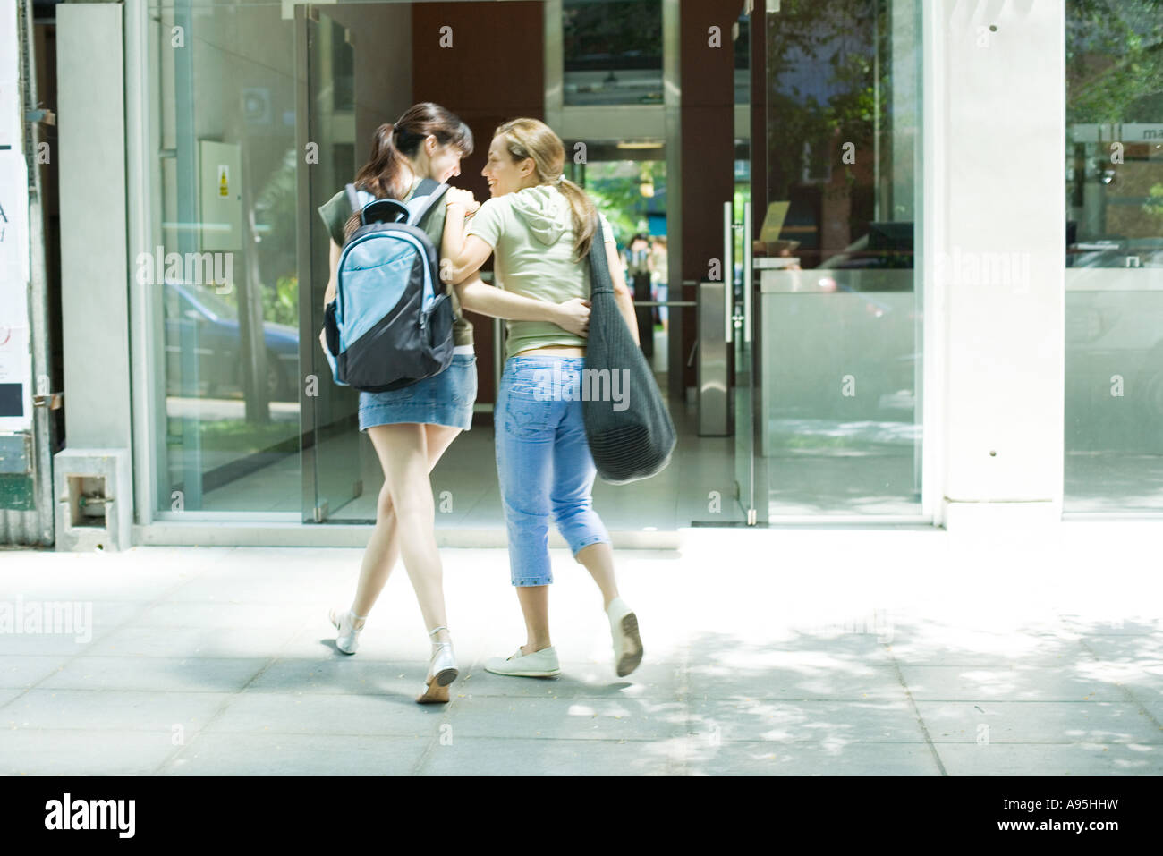 Two young women walking toward doorway together, arms around each other - Stock Image