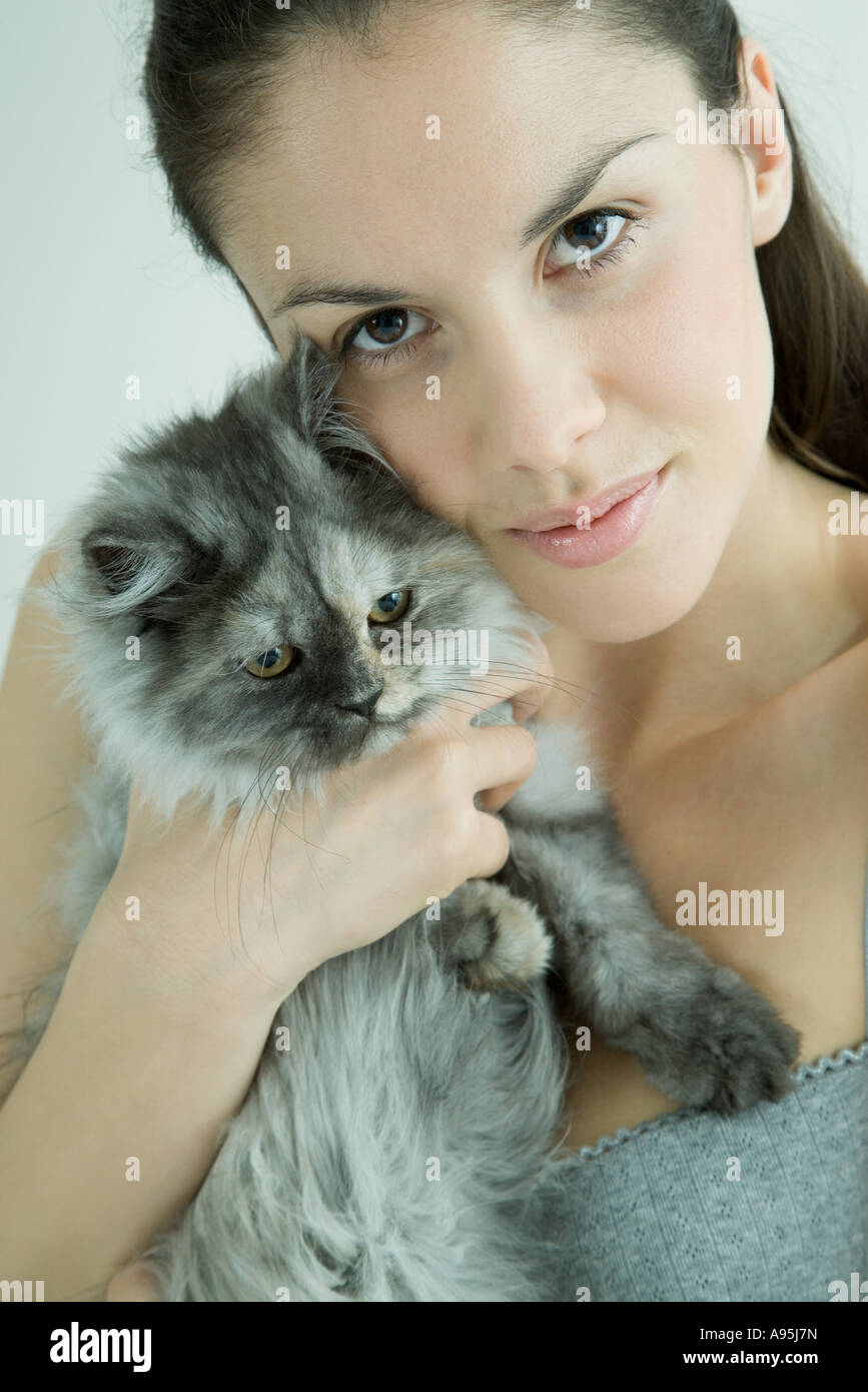 Young woman holding up cat to cheek, smiling at camera - Stock Image