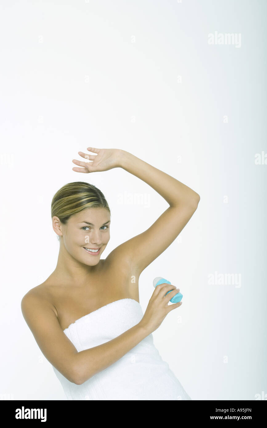 Woman putting on deodorant - Stock Image
