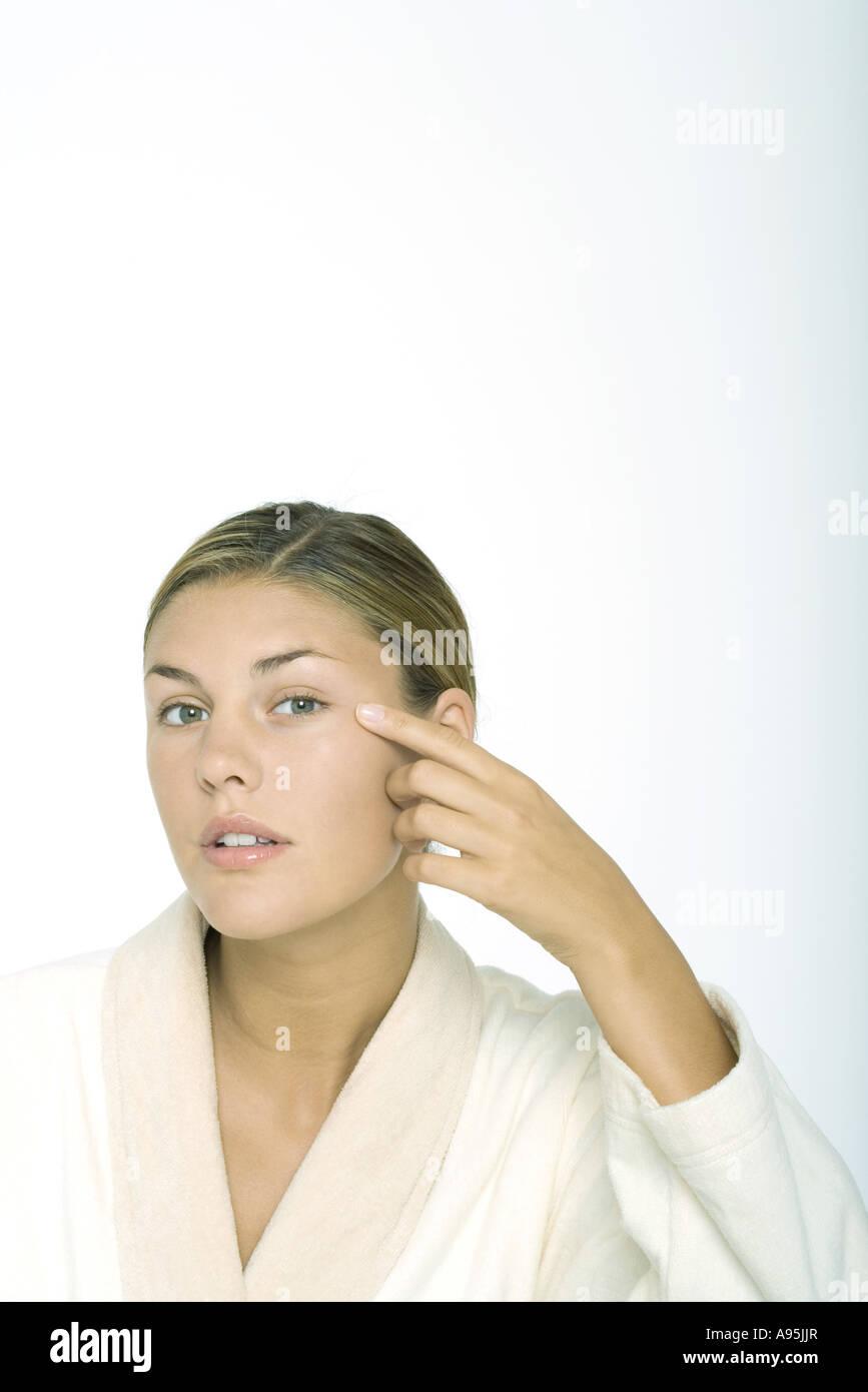 Young woman wearing bathrobe, touching corner of eye - Stock Image