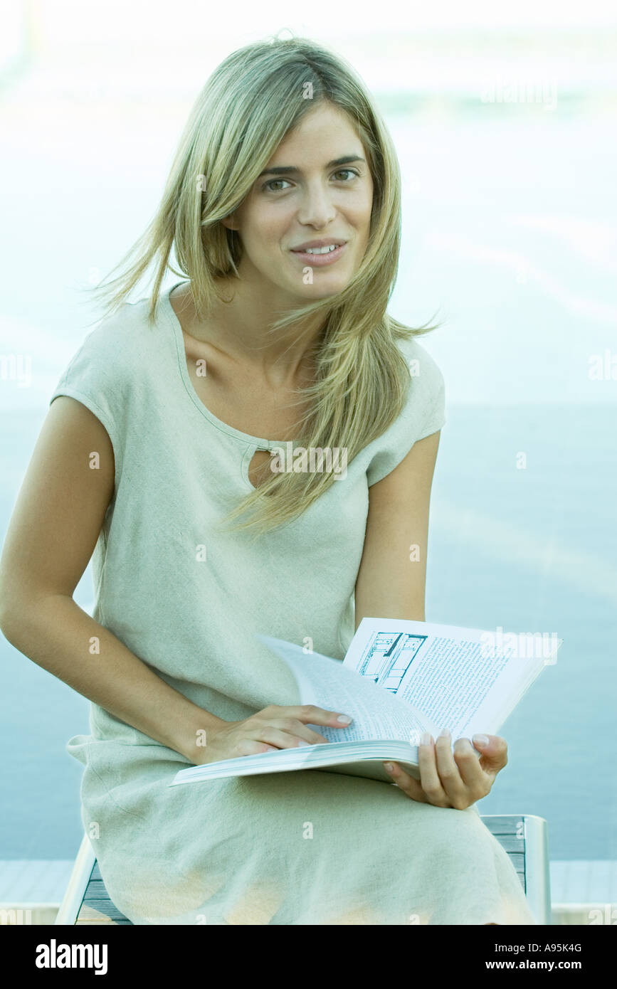 Woman sitting and holding book, water in background Stock Photo