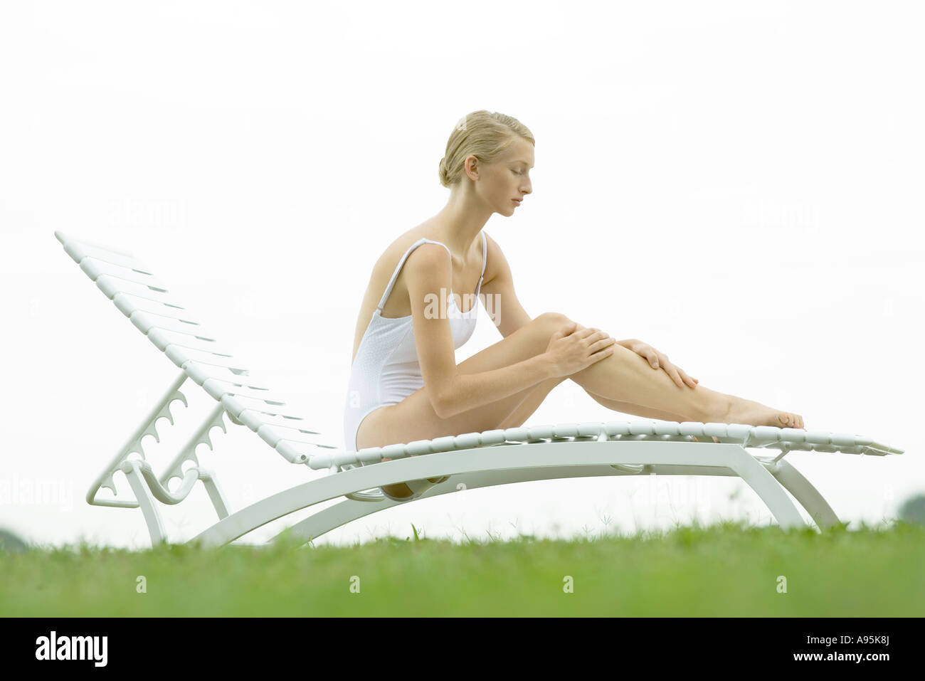Teenage girl sitting on lounge chair, hands on legs - Stock Image