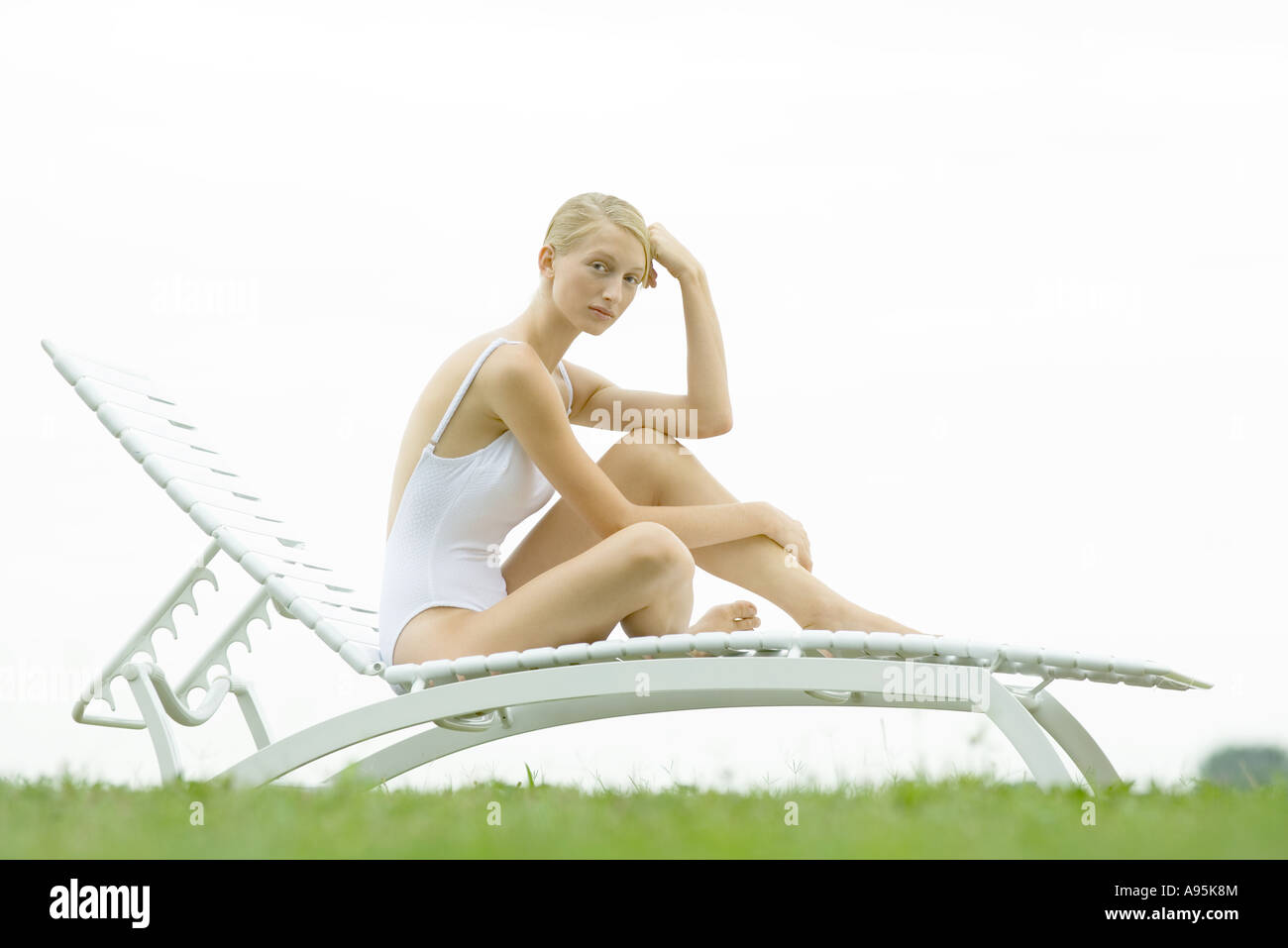 Teenage girl sitting on lounge chair, knee up, looking at camera - Stock Image