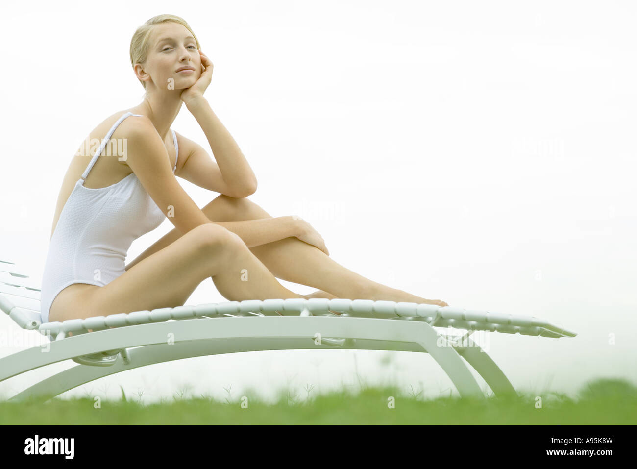 Teenage girl sitting on lounge chair, holding head, looking at camera - Stock Image