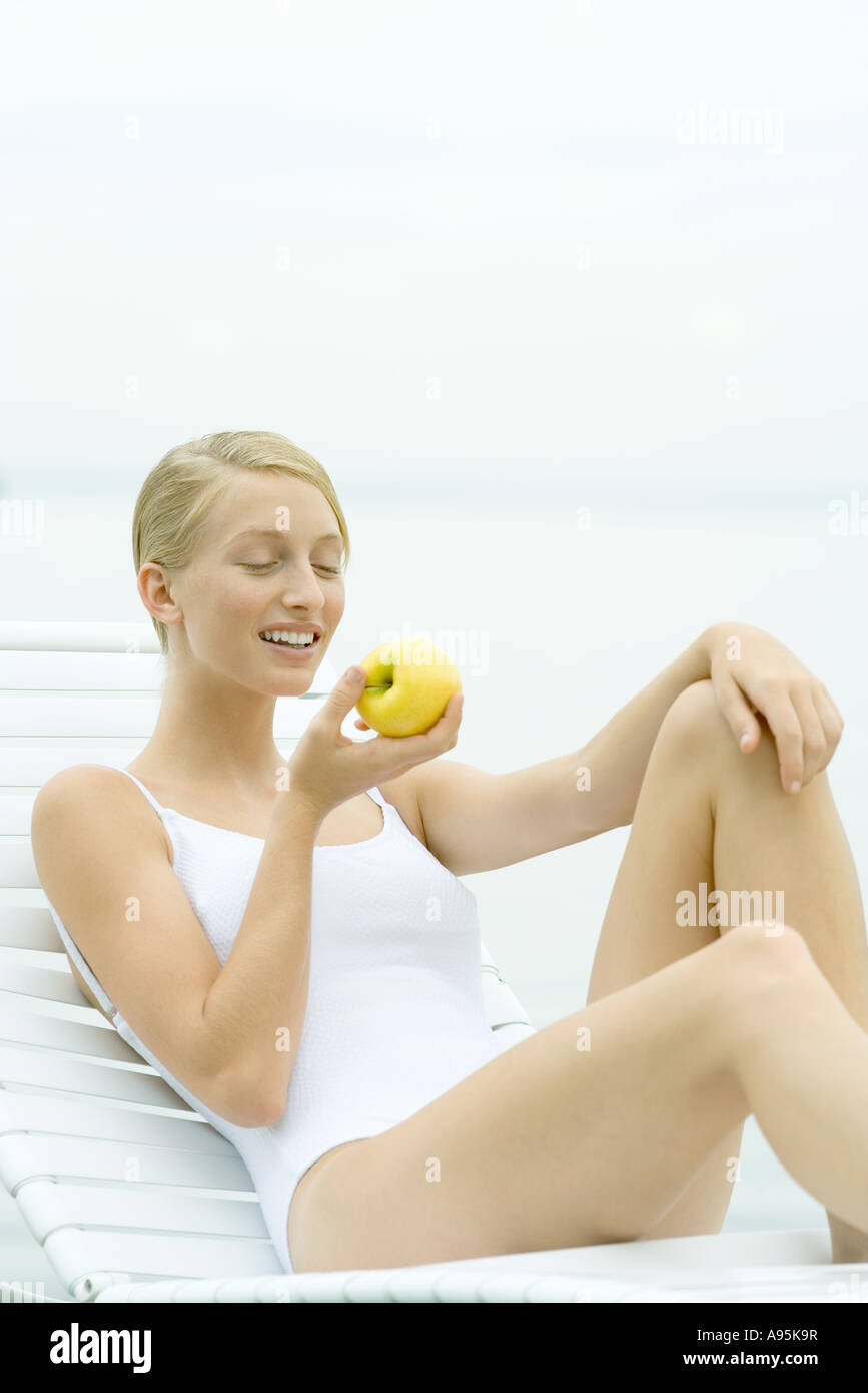 Teenage girl wearing bathing suit, sitting in lounge chair, eating apple - Stock Image