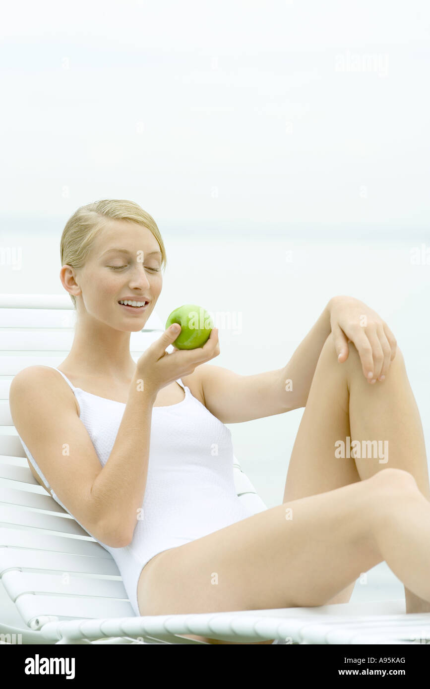 Teenage girl wearing bathing suit, sitting in lounge chair, holding apple - Stock Image