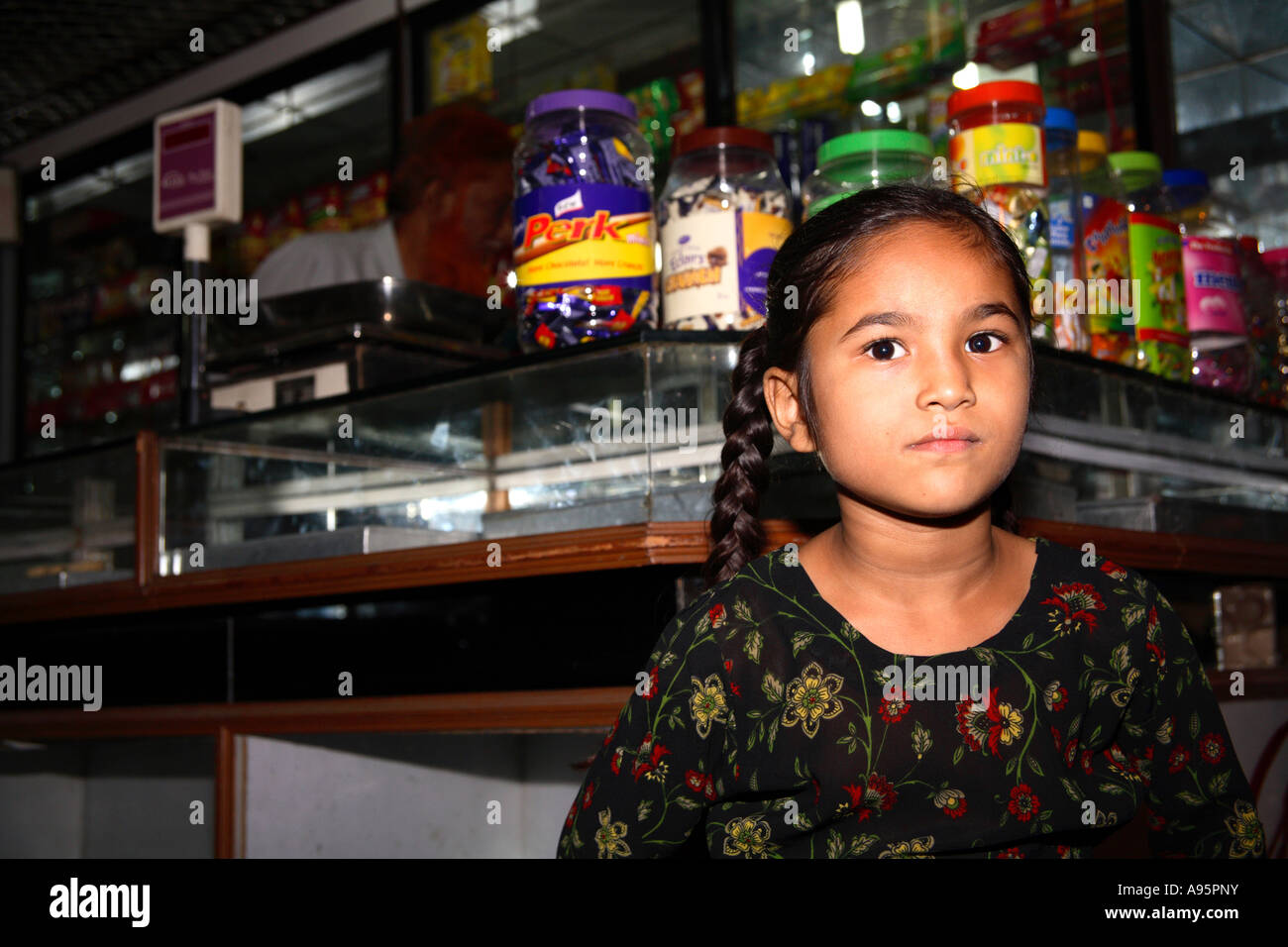 Young girl posing in confectionery shop, Ahmedabad, Gujarat, India - Stock Image