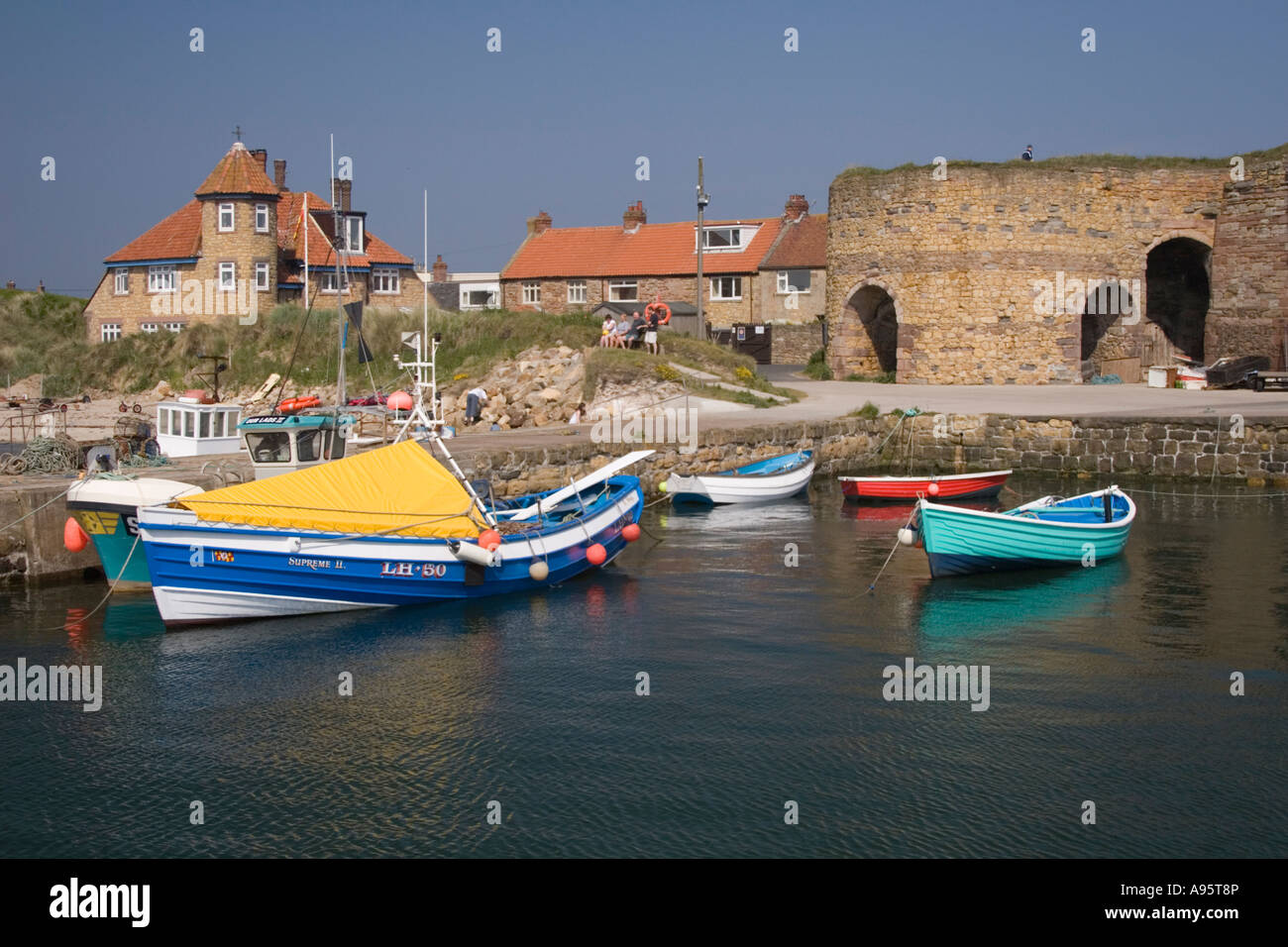 Several colorful boats in Beadnell harbour, Northumberland. - Stock Image