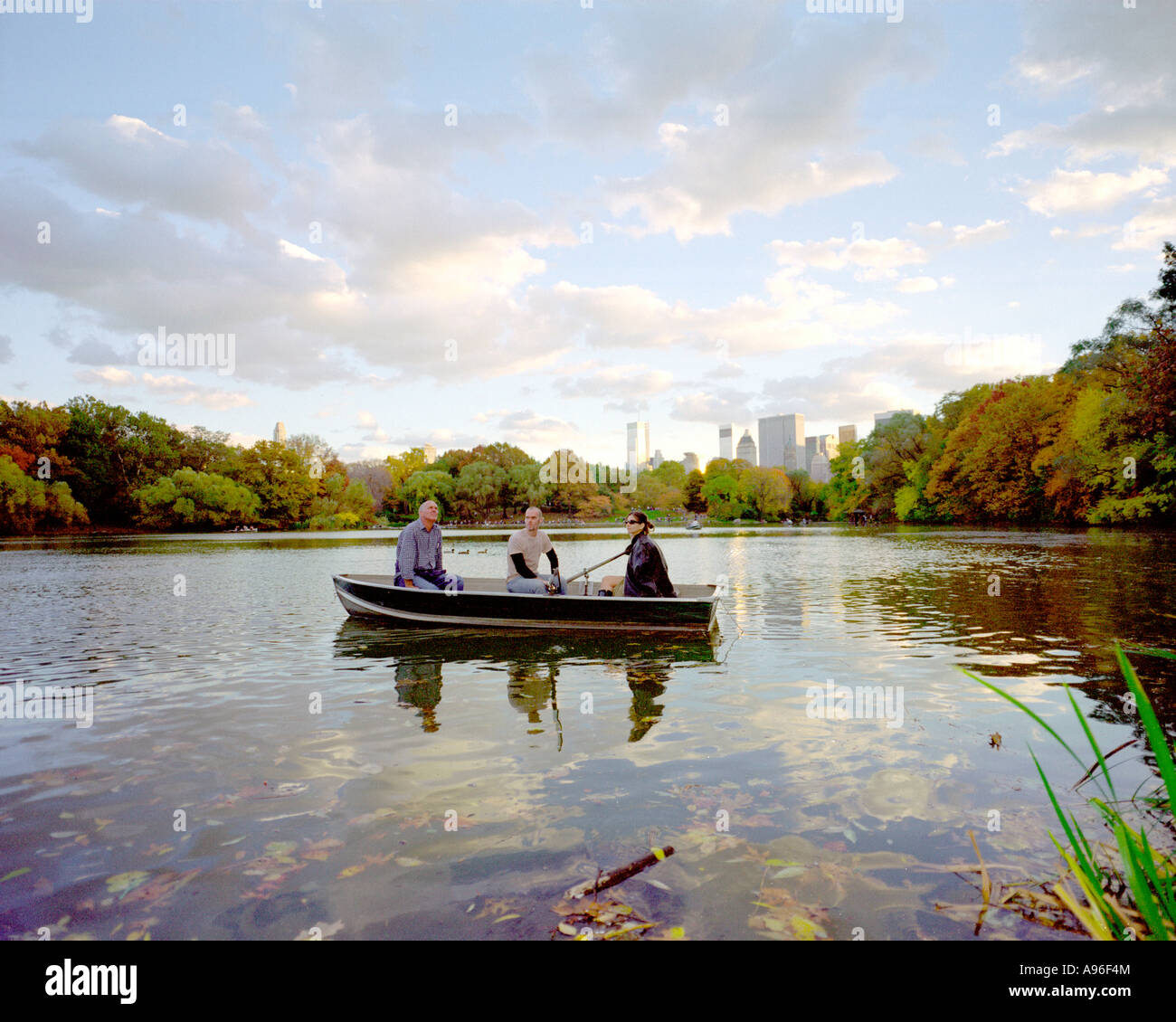 New Yorkers enjoy the early evening at a boating lake in Central Park New York, USA Stock Photo