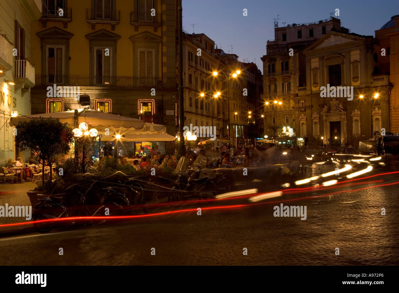 A nightscene in an Italian street shot with a long exposure to show the movement of traffic around the restaurant - Stock Image