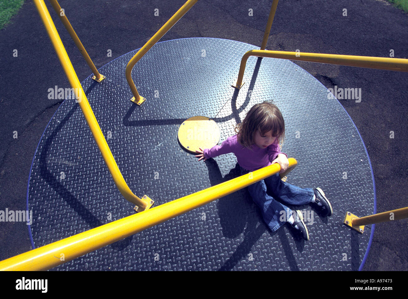 A small girl sits alone on a roundabout - Stock Image