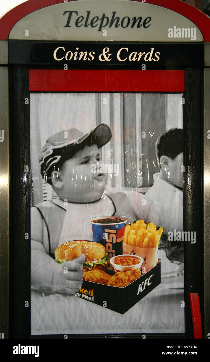 Protest poster against fatty food on the side of a phone box Brick Lane London - Stock Image