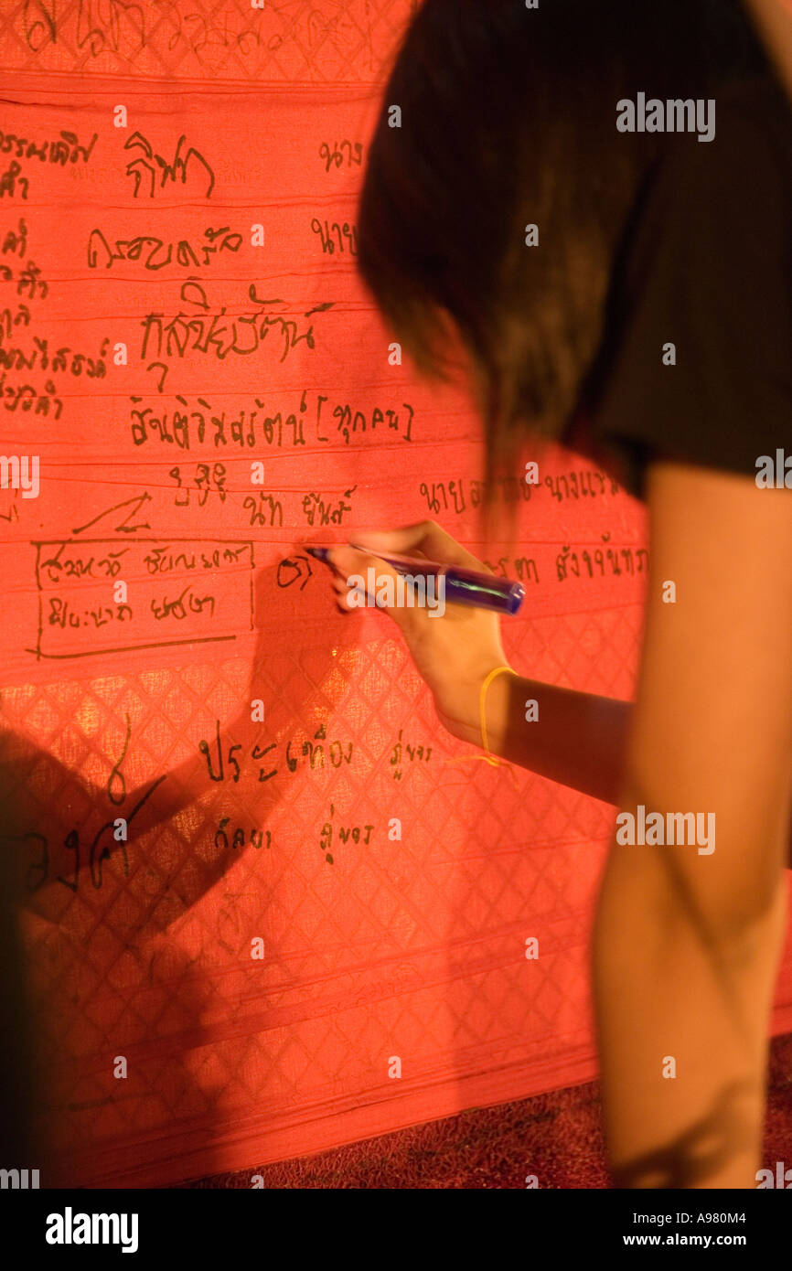 Young Thai woman writing prayers and wishes on saffron shroud at Golden Mount temple, Bangkok, Thailand - Stock Image