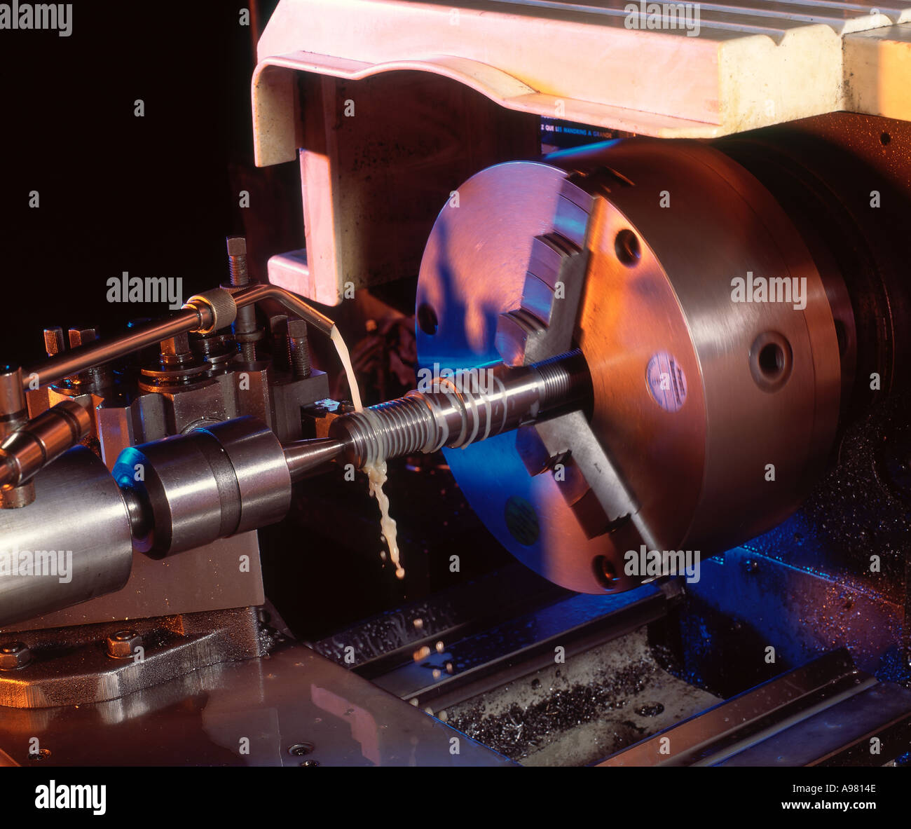 CLOSE UP VIEW OF LATHE CHUCK SHOWING CUTTING OF SCREW THREAD - Stock Image