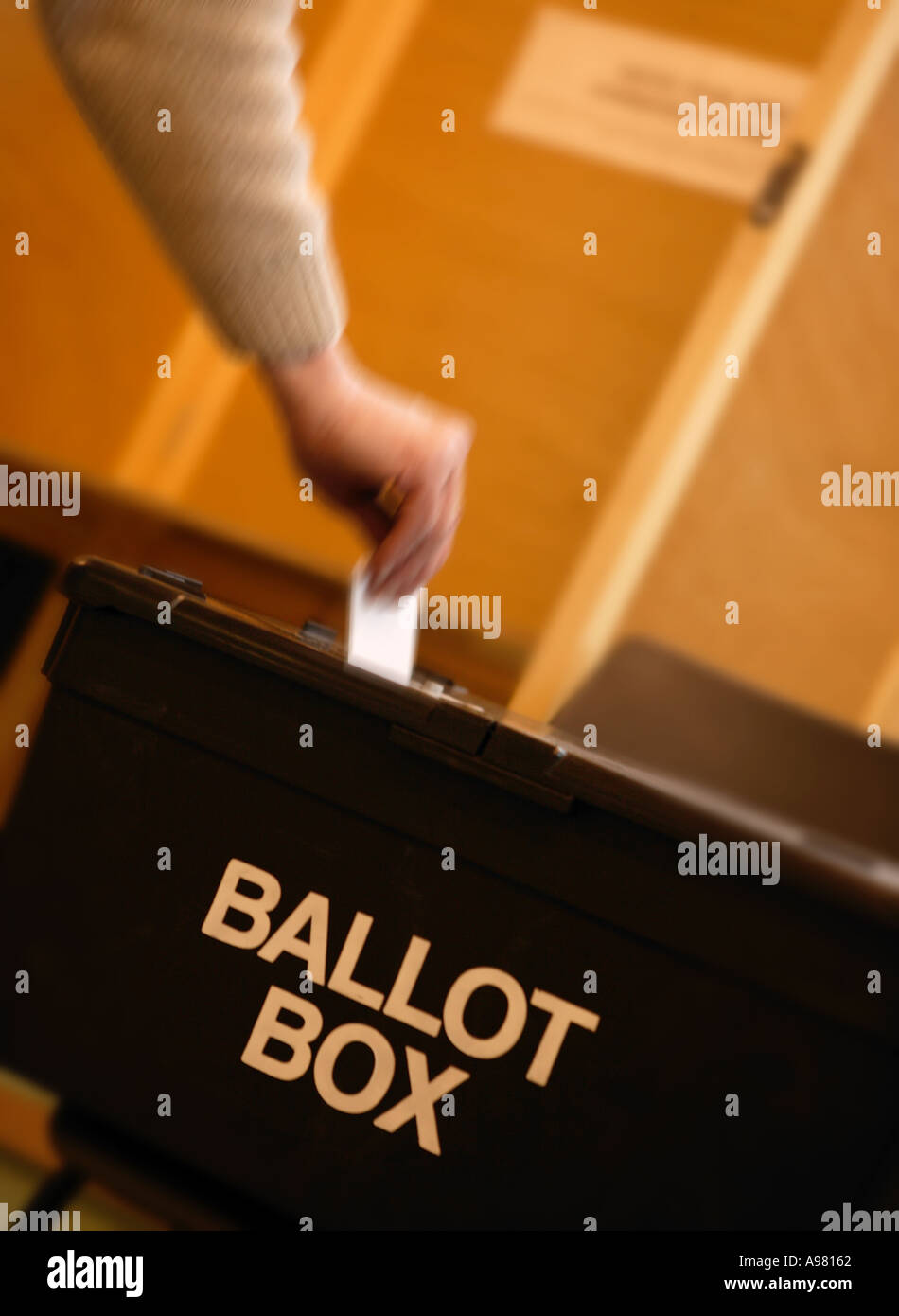 WHITE MAN MALE HAND PLACING VOTE INTO BALLOT BOX AT POLLING STATION - Stock Image