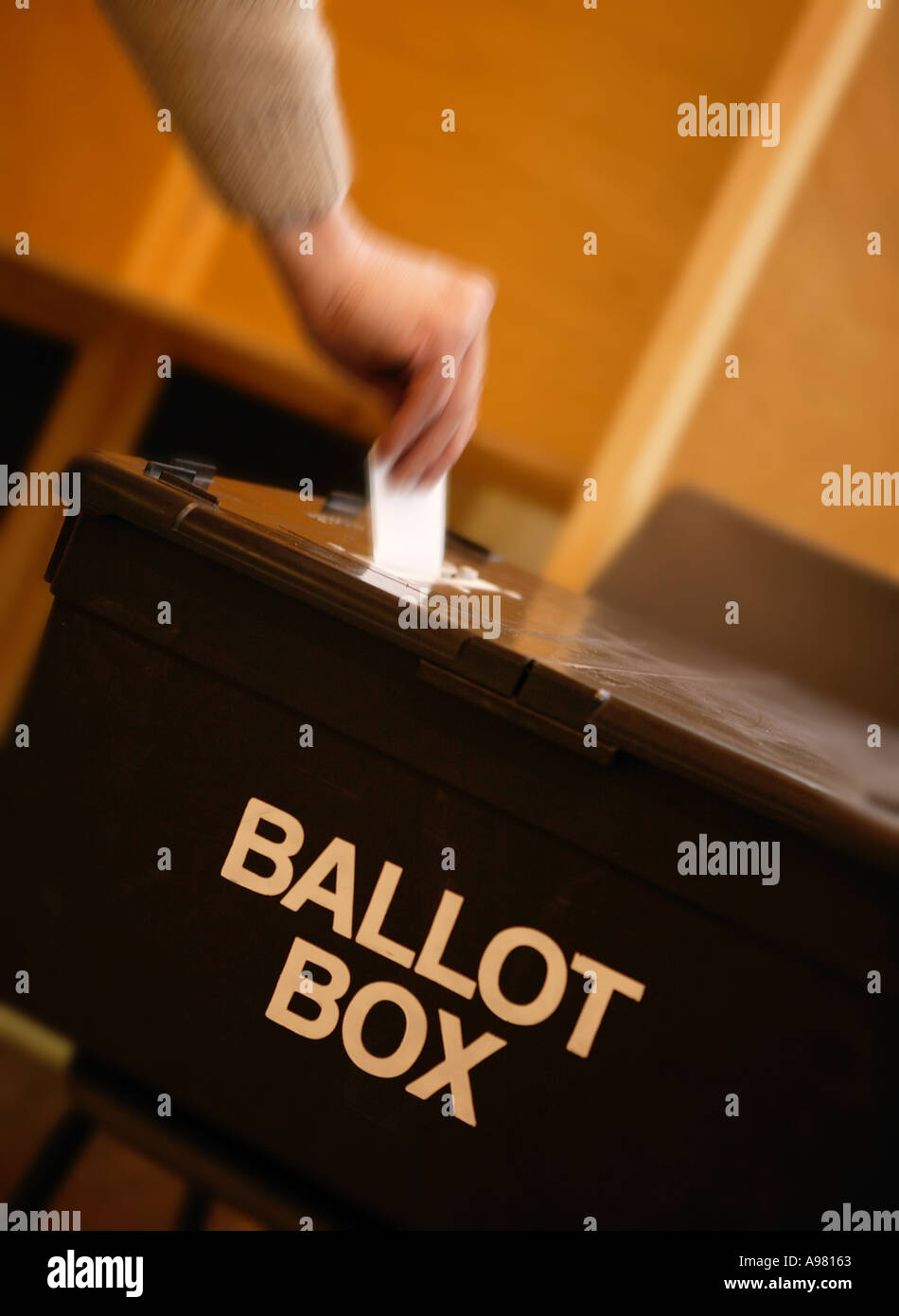 WHITE MALE HAND PLACING VOTE IN BALLOT BOX AT POLLING STATION - Stock Image