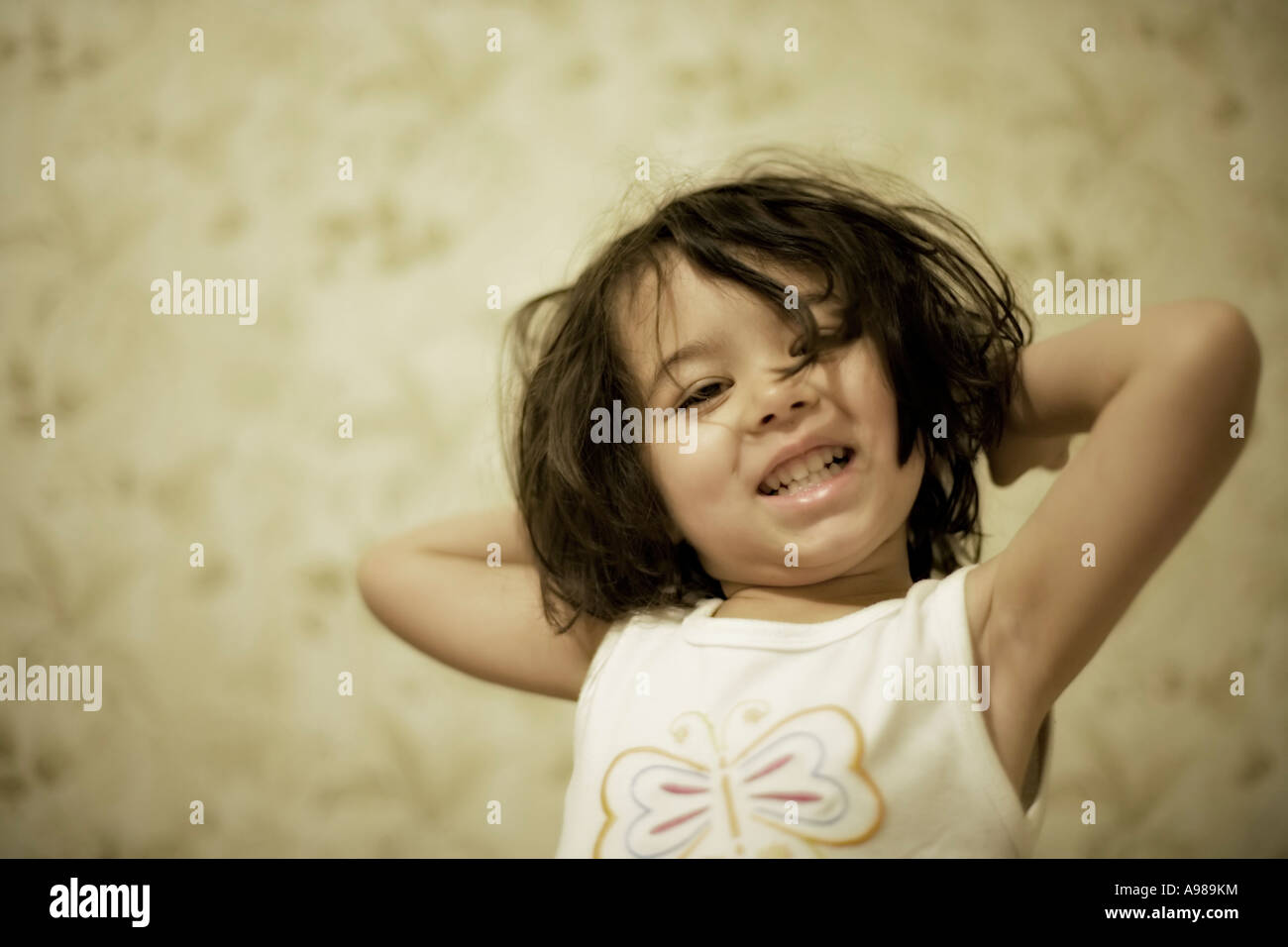 Girl wakes up and stretches - Stock Image