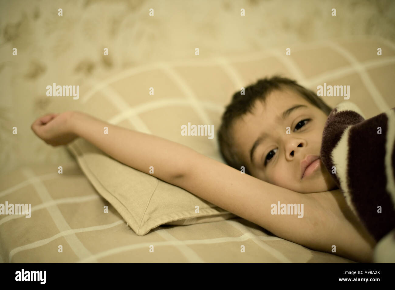 Boy aged 5 lies in bed unwell - Stock Image