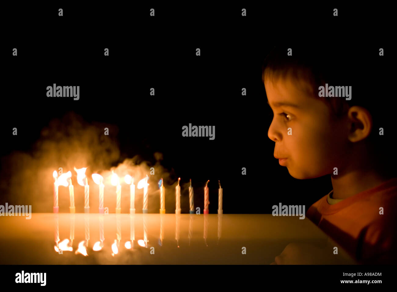 Boy aged 5 blows out 12 candles Stock Photo