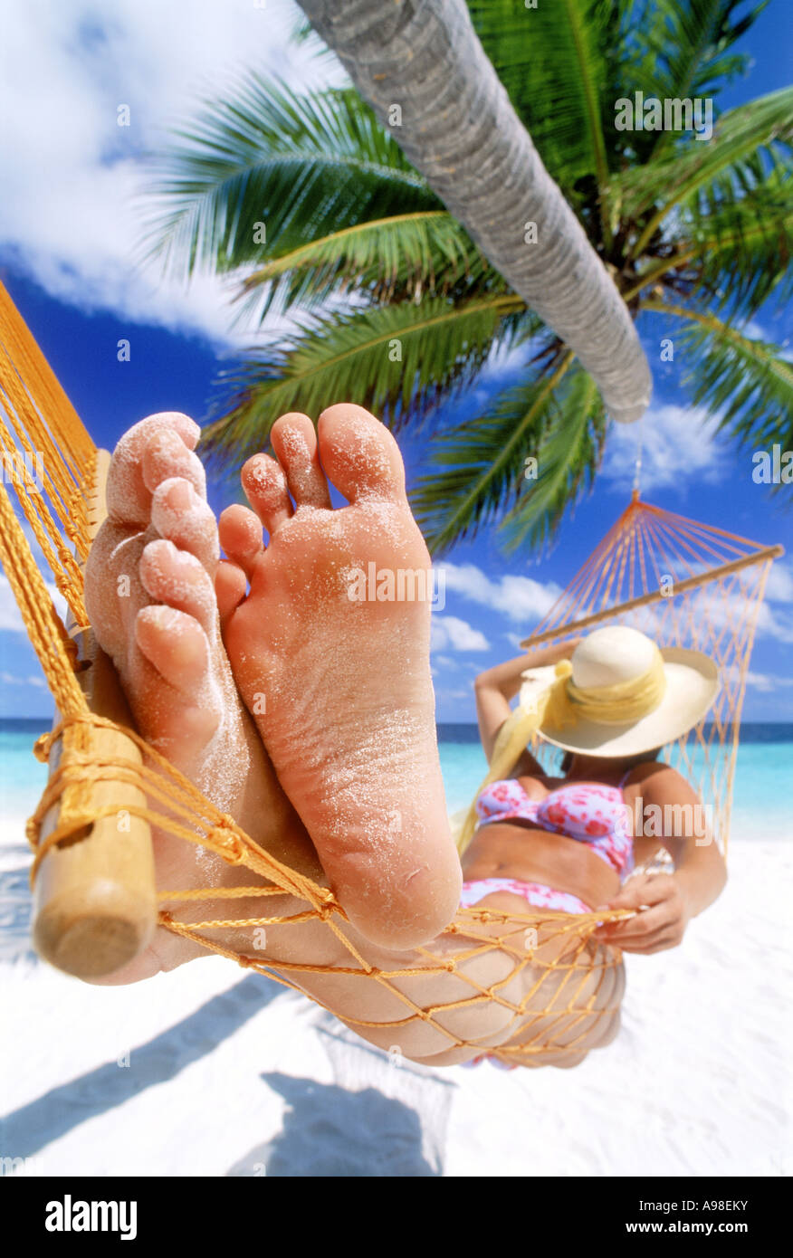 Woman with sandy feet resting in hammock under straw hat - Stock Image