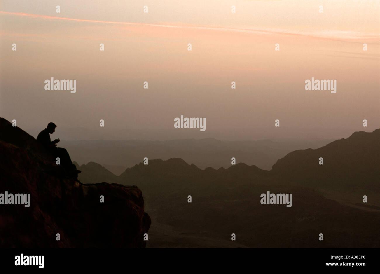 Sunrise in the Sinai desert Trekker sitting to the left of the frame silhouetted against the dawn EGYPT - Stock Image
