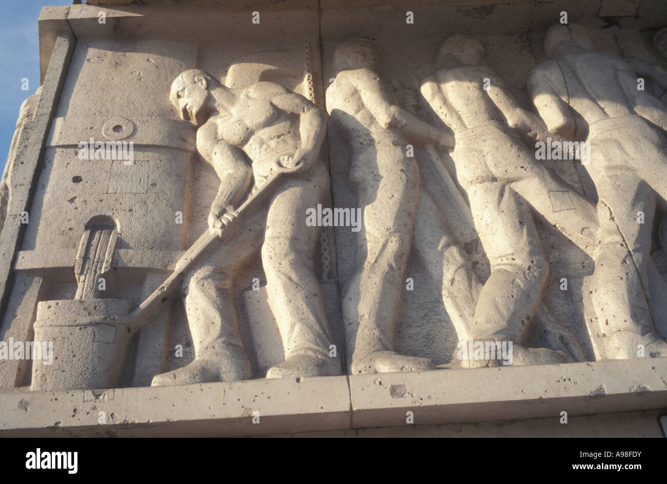 Relief of workers at steel foundry.  Soviet Realism art is on side of Budapest apartment building. - Stock Image