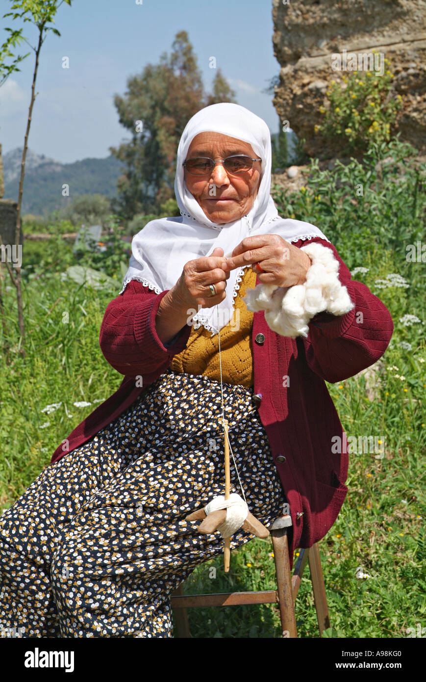 Turkish woman wearing a headcloth and spinning thread in the time honoured fashion Rural village near Antalya Turkey - Stock Image