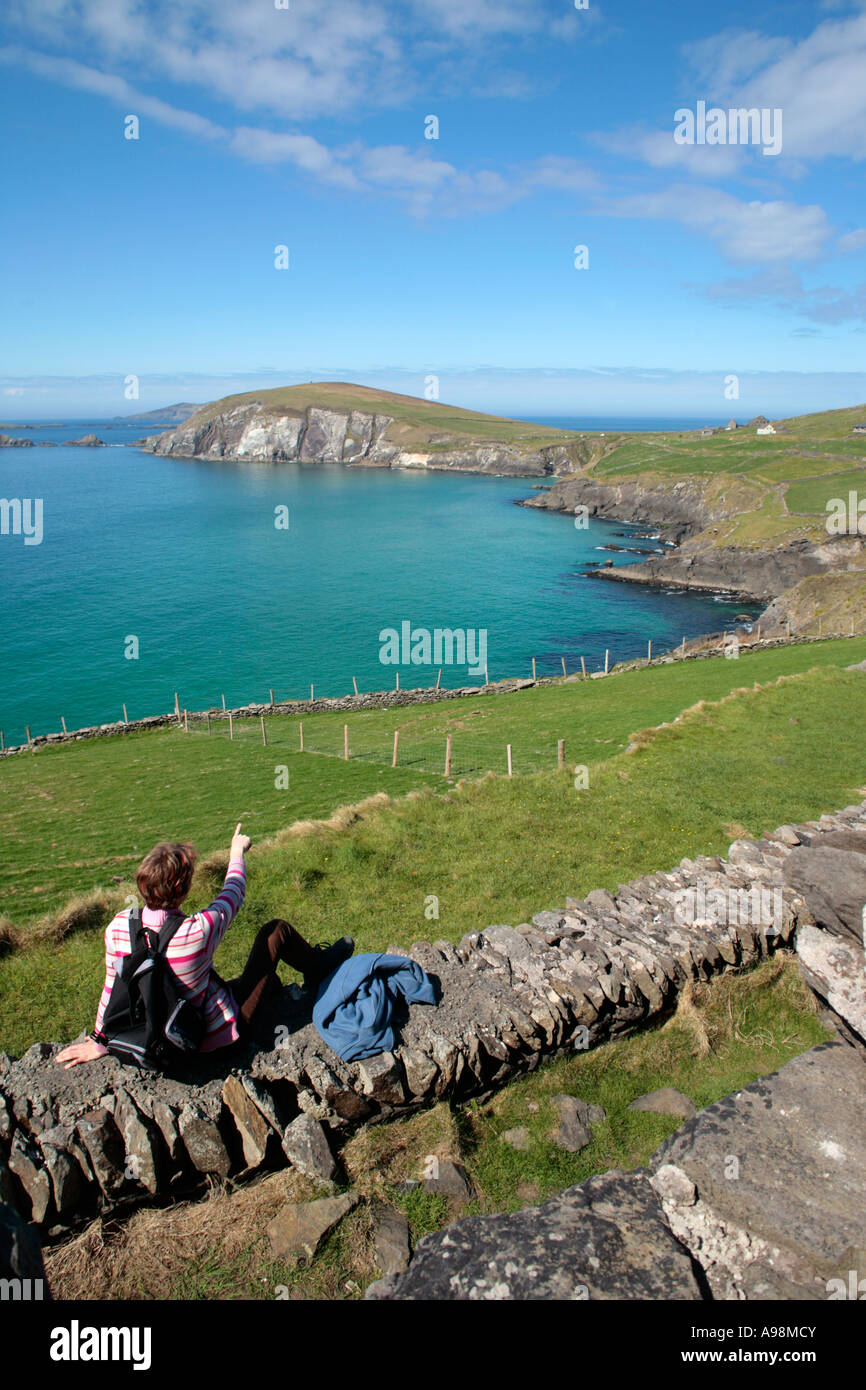 a young woman sitting in the sun enjoying the panoramic view of Slea Head on the Dingle Peninsula at the West Coast - Stock Image