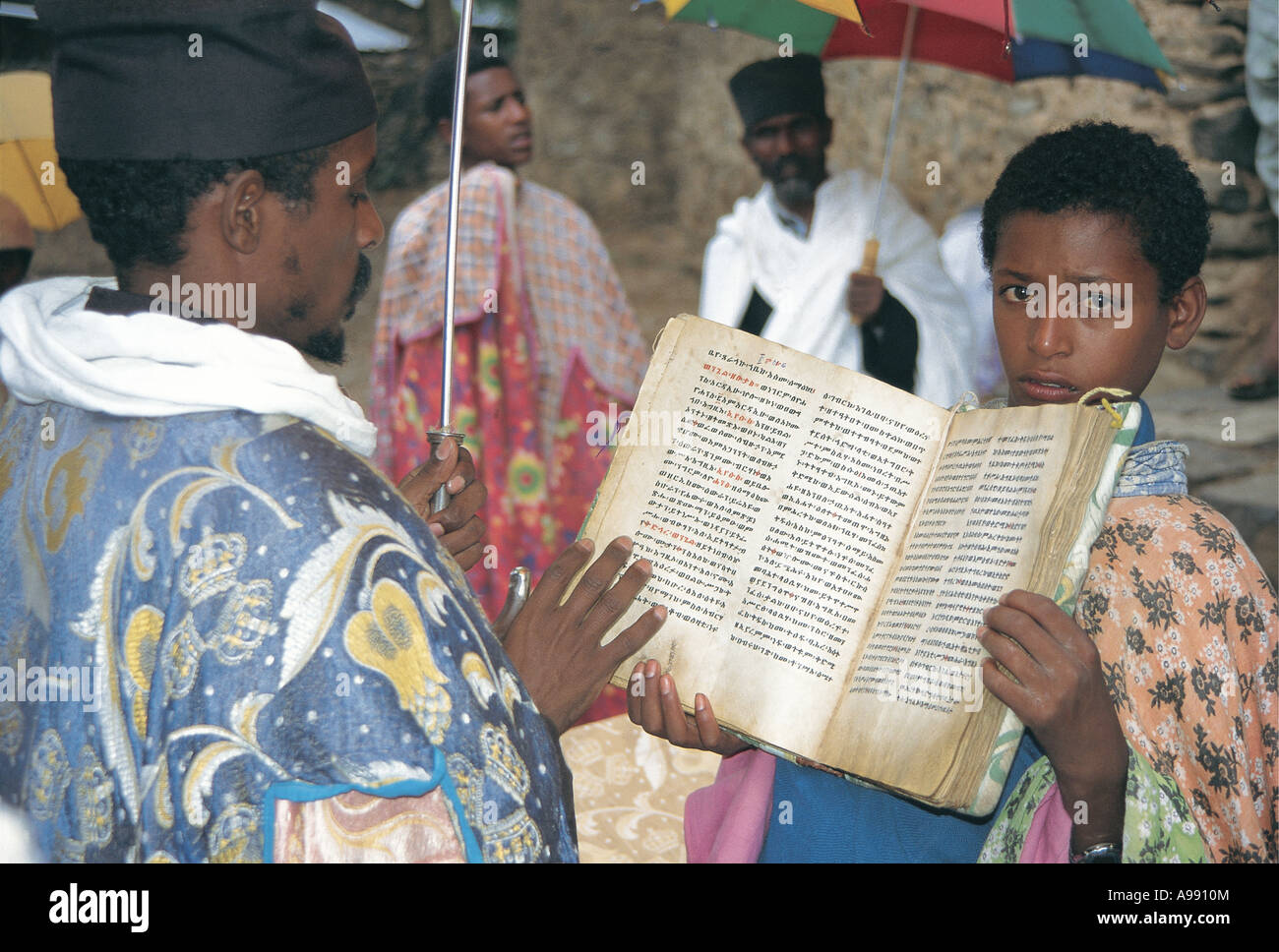 Young helper holding up book for reading Gondar Ethiopia - Stock Image